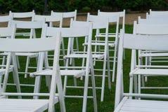 Weiße Stühle auf Hochzeitsort mit grünem Gras auf Hintergrund Hochzeitseinrichtung Hochzeitseinstellung Stockbilder