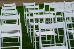 Weiße Stühle auf Hochzeitsort mit grünem Gras auf Hintergrund Hochzeitseinrichtung Hochzeitseinstellung Lizenzfreie Stockfotos