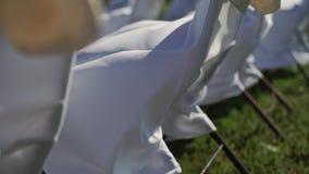 Weiße Stühle an der Feierhochzeitszeremonie draußen am windigen Tag des Sommers stock video
