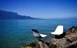 Weiße Stühle entlang dem See Stockbild