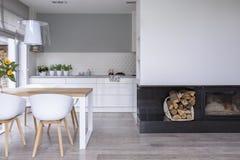 Weiße Stühle am Holztisch im modernen Esszimmerinnenraum mit Lampe und Kamin Reales Foto lizenzfreie stockfotografie