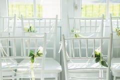 Weiße Stühle mit Blumen für eine Hochzeitszeremonie Stockfoto
