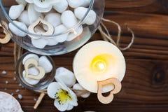 Weiße Steine in einem Glasvase, in den Blumen und in einer großen Kerze für Badekurort und Entspannung Stockbilder