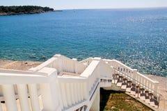 Weiße Steintreppe, die zu das Meer führt Stockbilder
