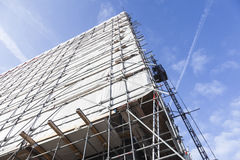 Weiße Stoff- und Metallpfosten des Baugerüsts gegen hohes neues buil Stockbilder