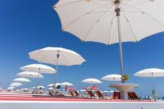 Weiße Strandregenschirme auf Rimini setzen, Italien auf den Strand Stockfotos