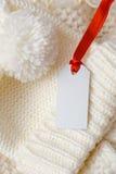 Weiße Strickmütze und Aufkleber mit rotem Band Stockfoto