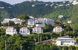 Weiße Stuck-Luxuseigentumswohnungen auf grünem tropischem Abhang Stockbild