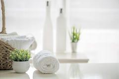 Weiße Tücher auf weißer Tabelle mit Kopienraum auf unscharfem Badezimmer Stockfoto