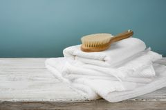 Weiße Tücher und Badebürste auf Holz über blauem Hintergrund Stockbilder