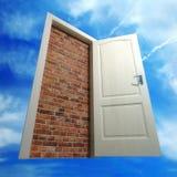 Weiße Tür setzte sich durch eine Maurerarbeit gegen den Himmel Lizenzfreie Stockfotografie