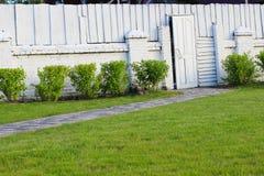 Weiße Tür und weißer Zaun des Ziegelsteines und des Holzes Lizenzfreies Stockbild