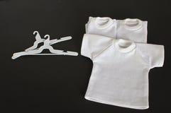 Weiße T-Shirts mit dem Kleiderbügel getrennt Stockfotografie