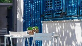 Weiße Tabelle nahe dem blauen Fenster stockfoto