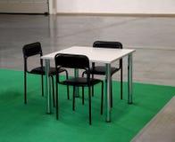 Weiße Tabelle und drei schwarze Stühle Lizenzfreies Stockfoto