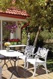 Weiße Tabelle und Stühle im Garten Lizenzfreie Stockbilder