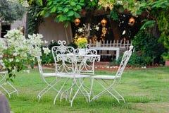 Weiße Tabelle und Stühle im schönen Garten. Stockbild