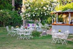 Weiße Tabelle und Stühle im schönen Garten. Lizenzfreies Stockfoto