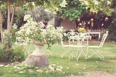 Weiße Tabelle und Stühle im schönen Garten Weinleseart pictur Stockbild