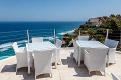 Weiße Tabellen und Stühle an einem Klippencafé im Freien mit Meerblick lizenzfreies stockbild