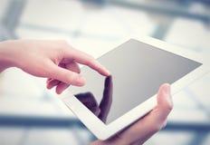 Weiße Tablette mit einem leeren Bildschirm in den Händen Stockfotografie