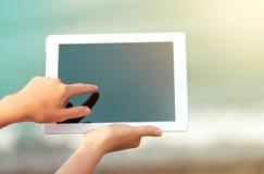 Weiße Tablette mit einem leeren Bildschirm in den Händen Stockbilder