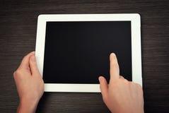 Weiße Tablette mit einem leeren Bildschirm in den Händen auf Tabelle Stockbilder