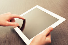 Weiße Tablette mit einem leeren Bildschirm in den Händen auf Tabelle Stockbild