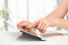Weiße Tablette mit einem leeren Bildschirm in den Händen auf Tabelle Stockfoto