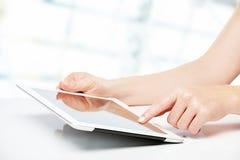 Weiße Tablette mit einem leeren Bildschirm in den Händen auf Tabelle Lizenzfreie Stockbilder