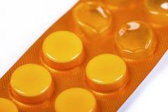 Weiße Tabletten in der orange Blisterpackung Lizenzfreie Stockbilder