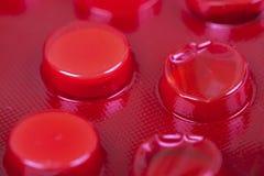 Weiße Tabletten in der roten Blisterpackung Stockfotografie