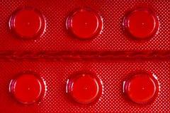 Weiße Tabletten in der roten Blisterpackung Lizenzfreies Stockbild