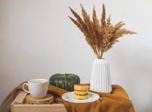 Weiße Tasse Kaffee-Cappuccino-Hüttenkäse-Pfannkuchen, gelbes Senf-Farbplaid, Schlafzimmer stockbilder