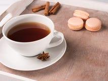 Weiße Tasse Tee auf dem Behälter mit macarons und Zichorie Lizenzfreie Stockbilder