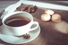 Weiße Tasse Tee auf dem Behälter mit macarons und Zichorie Stockfoto