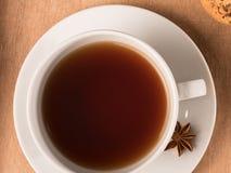 Weiße Tasse Tee auf dem Behälter mit Plätzchen Stockfoto