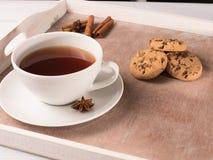 Weiße Tasse Tee auf dem Behälter mit Plätzchen und Zichorie Stockfotografie