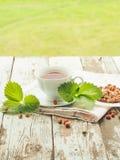 Weiße Tasse Tee auf einem Holztisch Lizenzfreies Stockbild