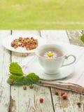 Weiße Tasse Tee auf einem Holztisch Stockbild