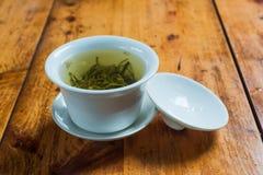 Weiße Tasse Tee auf einer hölzernen Tabelle in China Lizenzfreie Stockbilder