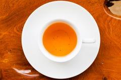 Weiße Tasse Tee auf hölzerner Tabelle Lizenzfreie Stockbilder