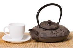 Weiße Tasse Tee auf Untertassen- und Eisenteekanne auf hölzerner Matte lizenzfreie stockfotos