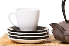 Weiße Tasse Tee auf verschiedenen Untertassen mit Eisenteekanne auf hölzernem stockfotografie