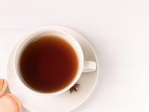 Weiße Tasse Tee mit macarons Stockbilder