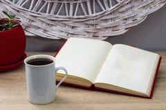 Weiße Tasse Tee und ein offenes Buch auf einem Holztisch Ein roter Topf mit grünem Baum im Hintergrund Lizenzfreies Stockbild