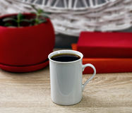 Weiße Tasse Tee und ein offenes Buch auf einem Holztisch Ein roter Topf mit grünem Baum im Hintergrund Stockfotos