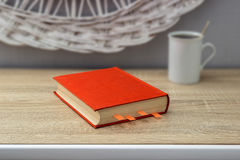Weiße Tasse Tee und ein offenes Buch auf einem Holztisch Ein roter Topf mit grünem Baum im Hintergrund Stockfoto