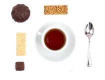 Weiße Tasse Tee und eine Auswahl von Bonbons Stockbilder