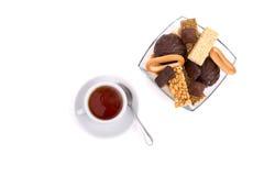Weiße Tasse Tee und eine Auswahl von Bonbons Stockbild